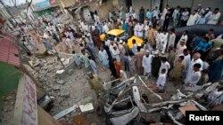 Warga Karachi berkumpul dekat kendaraan-kendaraan yang rusak akibat ledakan bom di kantor Partai Nasional Awami (ANP), Sabtu (27/4).
