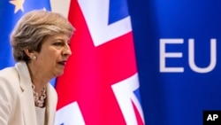 FILE - British Prime Minister Theresa May prepares to address a media conference at an EU summit in Brussels, June 23, 2017. More than six months have passed since Britain triggered the two-year countdown to its EU exit but separation talks are mired in details.