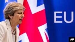 FILE - British Prime Minister Theresa May prepares to address a press conference at an EU summit in Brussels, June 23, 2017.