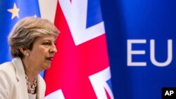 FILE - British Prime Minister Theresa May prepares to address a media conference at an EU summit in Brussels, June 23, 2017.