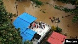 Người dân đợi hàng cứu trợ trên mái nhà của họ tại một khu vực bị ngập lụt ở bang Kerala miền nam, Ấn Độ, ngày 17 tháng 8, 2018.