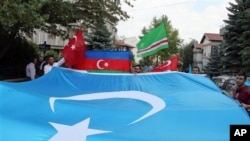 FILE - Uighurs living in Turkey carry a blue flag with a white star and a crescent representing Eastern Turkistan in Ankara, Turkey, July 5, 2012.