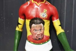 A Ghanaian football fan shows off his body painting, containing the image of star player Michael Essien