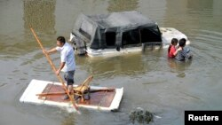 A man (L) paddles a makeshift raft as residents walks past a partially submerged car on a flooded street in Yuyao, Zhejiang province, Oct.11, 2013.