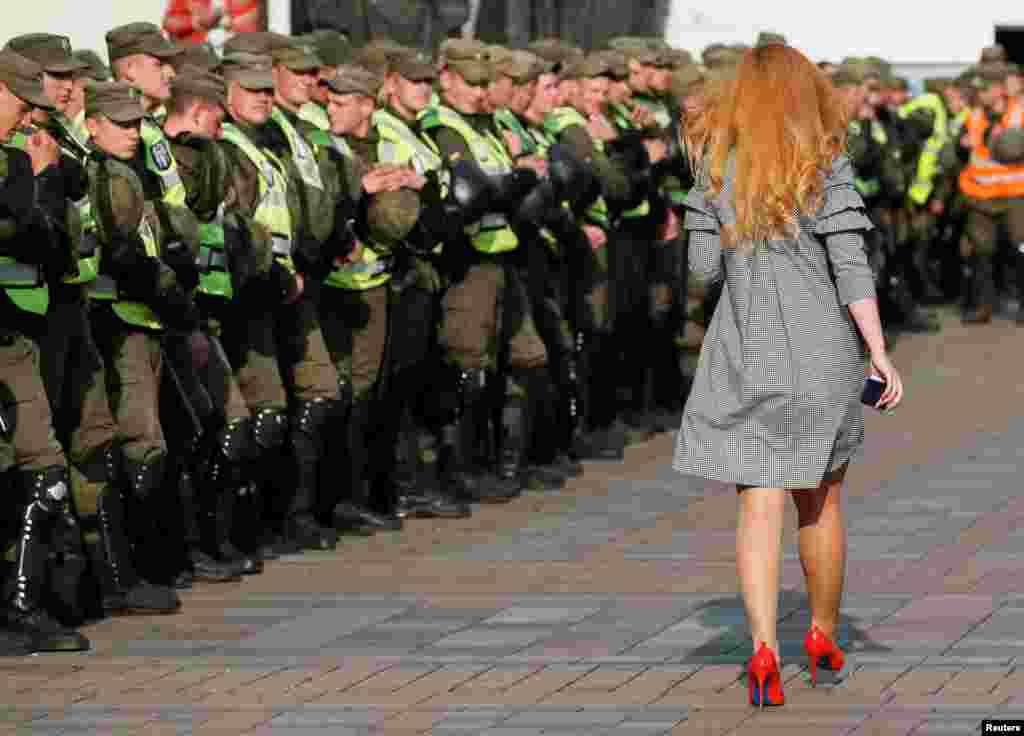 A woman walks past servicemen of the National Guard in front of Ukrainian Parliament during a opposition rally in Kyiv.