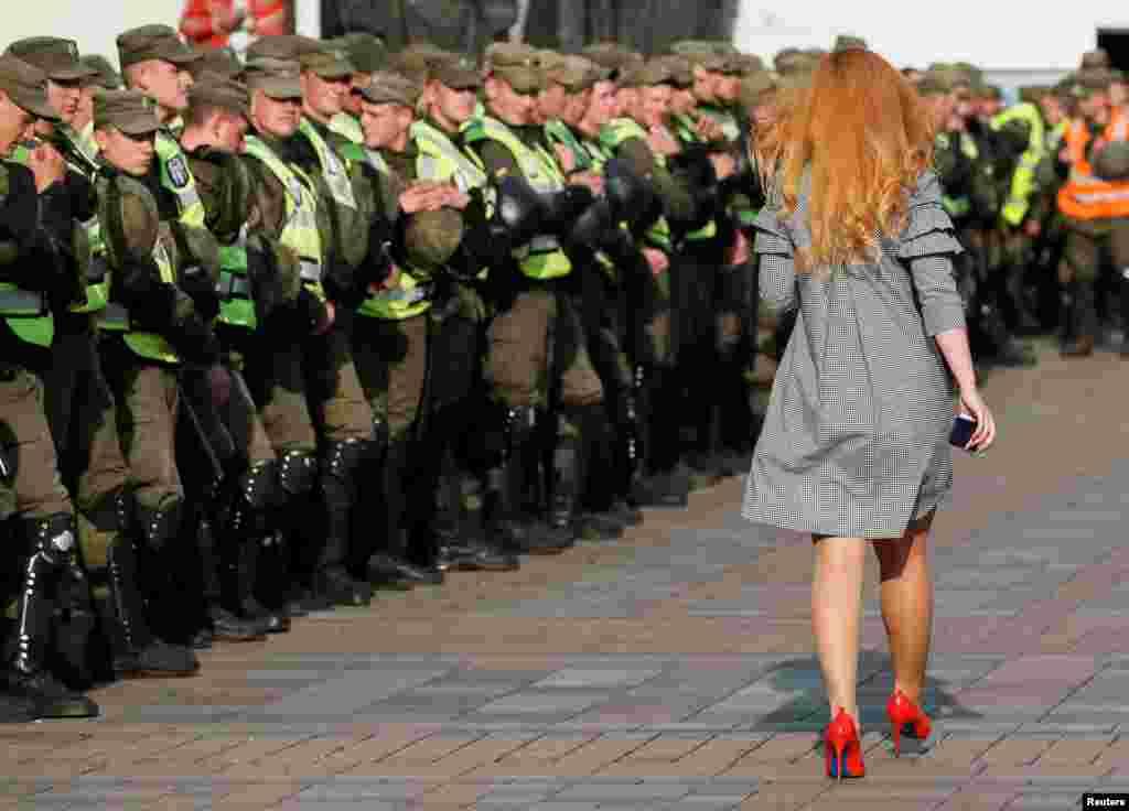 Seorang perempuan berjalan melewati para anggota militer Ukraina di depan gedung parlemen, saat aksi unjuk rasa kelompok oposisi di Kyiv, Ukraina.