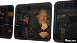 WikiLeaks founder Julian Assange is seen in a police van after he was arrested by British police outside the Ecuadorian embassy in London, April 11, 2019.