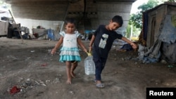 Children carry a drinking water container after filling it from a municipal tap under a flyover at a slum area in Kolkata, India, May 26, 2016.