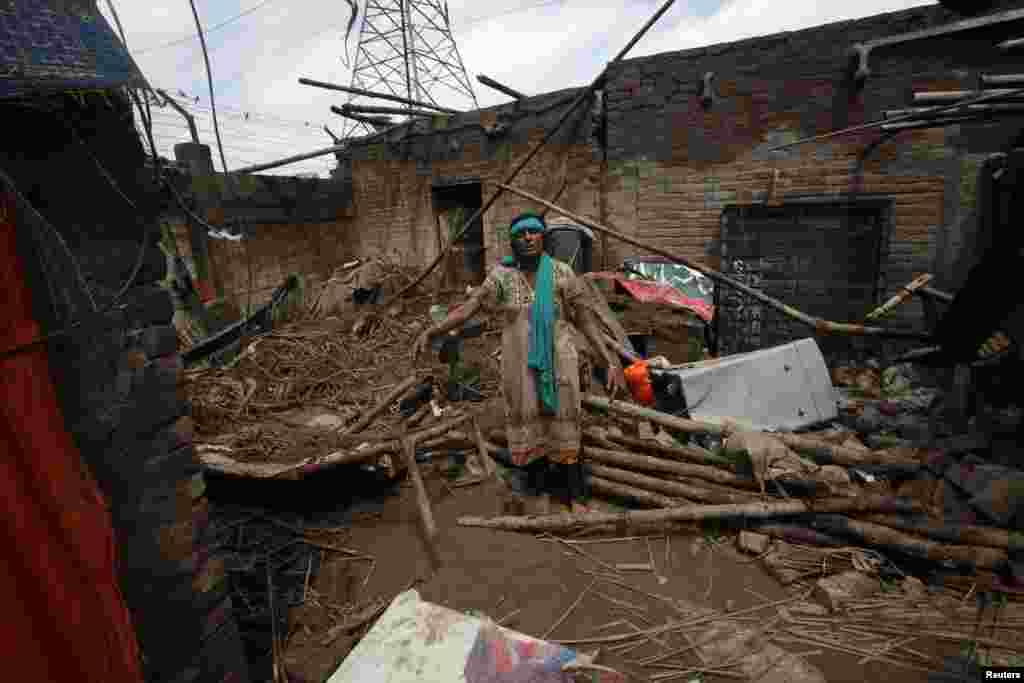 Pakistani woman Mumtaz Bibi stands in her partially-destroyed house following heavy rain in Lahore, Sept. 6, 2014.