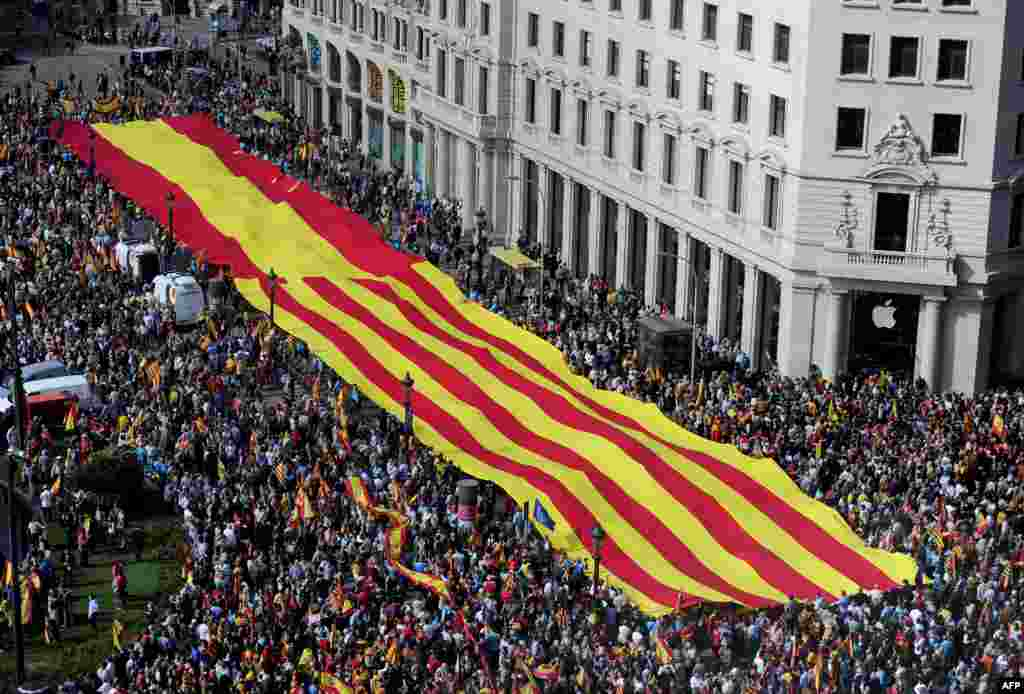 Anti-independentist Catalans hold a giant banner with a Catalan flag and a Spanish flag during a demonstration at Catalunya square in Barcelona, Spain.Tens of thousands of people demonstrated in Barcelona for the unity of Spain and against the independence of Catalonia on the occasion of the National Day.