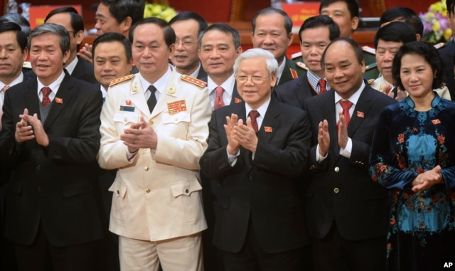 Newly re-elected Vietnam Communist Party General Secretary Nguyen Phu Trong, center front, flanked by Politburo members Tran Dai Quang, second left, Nguyen Xuan Phuc, second right, and Nguyen Thi Kim Ngan, right, at the closing ceremony in Hanoi, Jan. 28, 2016.