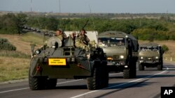 Russian military vehicles maneuver on a road 9 miles from the Ukrainian border in the Rostov-on-Don region, Russia, Aug. 15, 2014. (AP Photo/Pavel Golovkin)