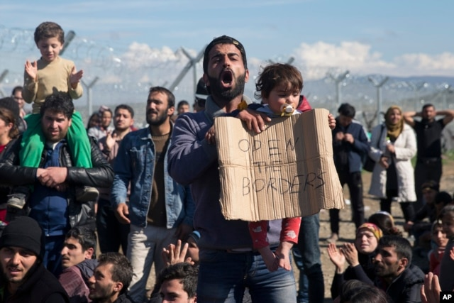 FILE - Stranded refugees and migrants protest in front of the wire fence that separates the Greek side from the Macedonian one at the northern Greek border station of Idomeni, Feb. 27, 2016.