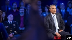 President Barack Obama watches the replay of his emotional speech from earlier this week during a CNN televised town hall meeting at George Mason University in Fairfax, Va., Thursday, Jan. 7, 2016.