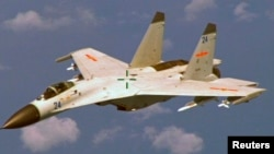 """A Chinese J-11 fighter jet is seen flying near a U.S. Navy P-8 Poseidon about 215 km (135 miles) east of China's Hainan Island in this U.S. Department of Defense handout photo taken August 19, 2014. China on Saturday called US criticism of an approach by one of its jets to a US Navy patrol plane off the Chinese coast earlier this week """"completely groundless"""" and said its pilot had maintained a safe distance from the US aircraft. Picture taken August 19, 2014. REUTERS/U.S. Navy/Handout"""
