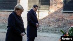 """Kancealrka Merkel i premijer Poljske Mateuš Moravijecki polažu vence ispred """"zida smrti"""" u bivšem nacističkom logoru Aušvic-Birkenau, u Poljskoj (Foto: Reuters/Kacper Pempel)"""
