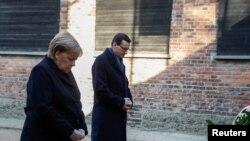 """Kancelarja gjermane Angela Merkel dhe Kryeministri polak Mateusz Morawiecki duke vënë kurora tek """"muri i vdekjes"""" në ish-kampin nazist të Aushvicit (Oswiecim, Poloni, 6 dhjetor 2019)"""