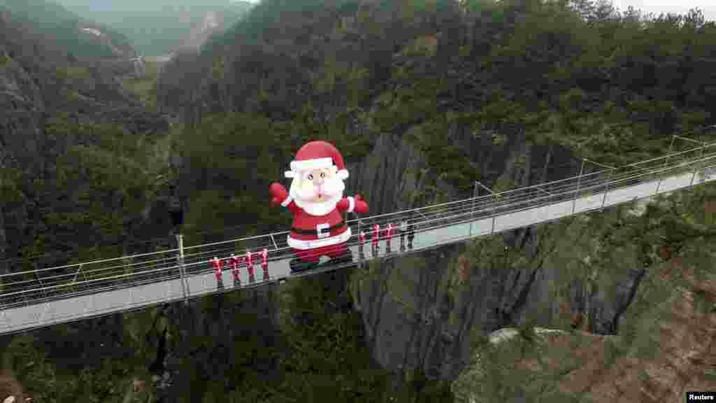 បាឡុងខ្យល់រូប Santa Claus ត្រូវបានតំឡើងនៅលើស្ពានកញ្ចក់ ដើម្បីអបអរពិធីបុណ្យ Christmas នៅឯកន្លែងសម្រាកលំហែកាយ Shiniuzhai ក្នុងខេត្ត Hunan ប្រទេសចិន កាលពីថ្ងៃទី២៣ ខែធ្នូ ឆ្នាំ២០១៥។