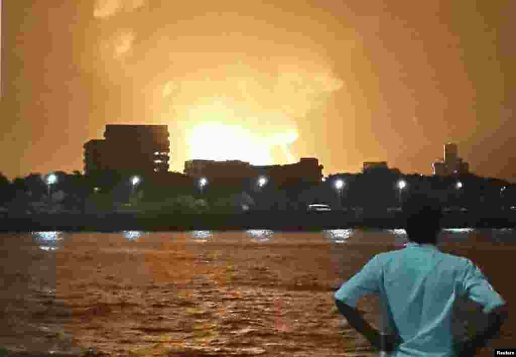 A man watches Indian Navy submarine INS Sindhurakshak on fire, Mumbai, August 14, 2013.