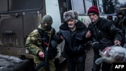 An elderly Ukrainian man is helped by an Ukrainian army soldier and a citizen during a evacuation of civilians in Debaltseve, in the Donetsk region, Feb. 3, 2015.