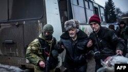 Vojnik ukrajinske vojske pomaže starijem gradjanimu tokom evakuacije civila u mestu Debalceve u regionu Donjecka, 3. februara 2015.
