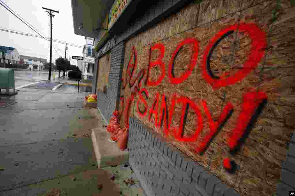 """The boarded up windows on a store front in Margate N.J., read """"Boo Sandy!"""", as the area prepares for the arrival of the superstorm, Sunday, Oct. 28, 2012."""