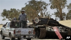 Rebel fighters armed with rocket propelled grenade launchers head back into Ajdabiya, past a previously destroyed pro-Gadhafi forces tank, during heavy shelling there, in Libya, April 10, 2011