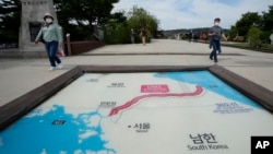 Visitors walk by a map of two Koreas showing North Korea's capital Pyongyang and South Korea's capital Seoul at the Imjingak Pavilion in Paju, near the border with North Korea, South Korea, Sept. 24, 2021.