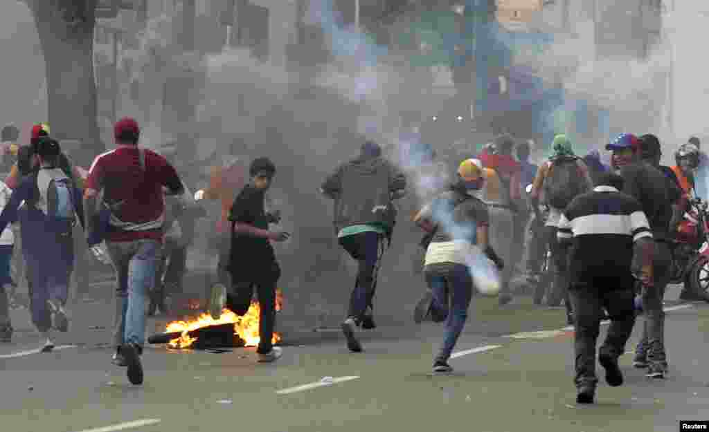 Supporters of opposition leader Henrique Capriles run away from tear gas fired by riot police as they demonstrated for a recount of the votes in Sunday's election, in Caracas, April 15, 2013.