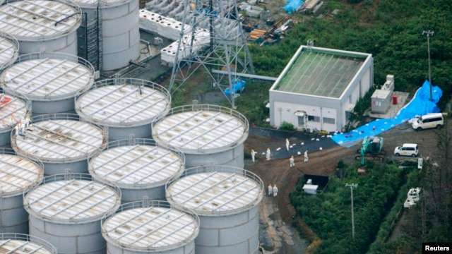 An aerial view shows workers wearing protective suits and masks working atop contaminated water storage tanks at Tokyo Electric Power Co. (TEPCO)'s tsunami-crippled Fukushima Daiichi nuclear power plant in Fukushima, August 20, 2013.