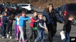 Connecticut State Police lead a line of children from the Sandy Hook Elementary School in Newtown, Conn. on Friday, Dec. 14, 2012 after a shooting at the school. (AP Photo/Newtown Bee, Shannon Hicks)