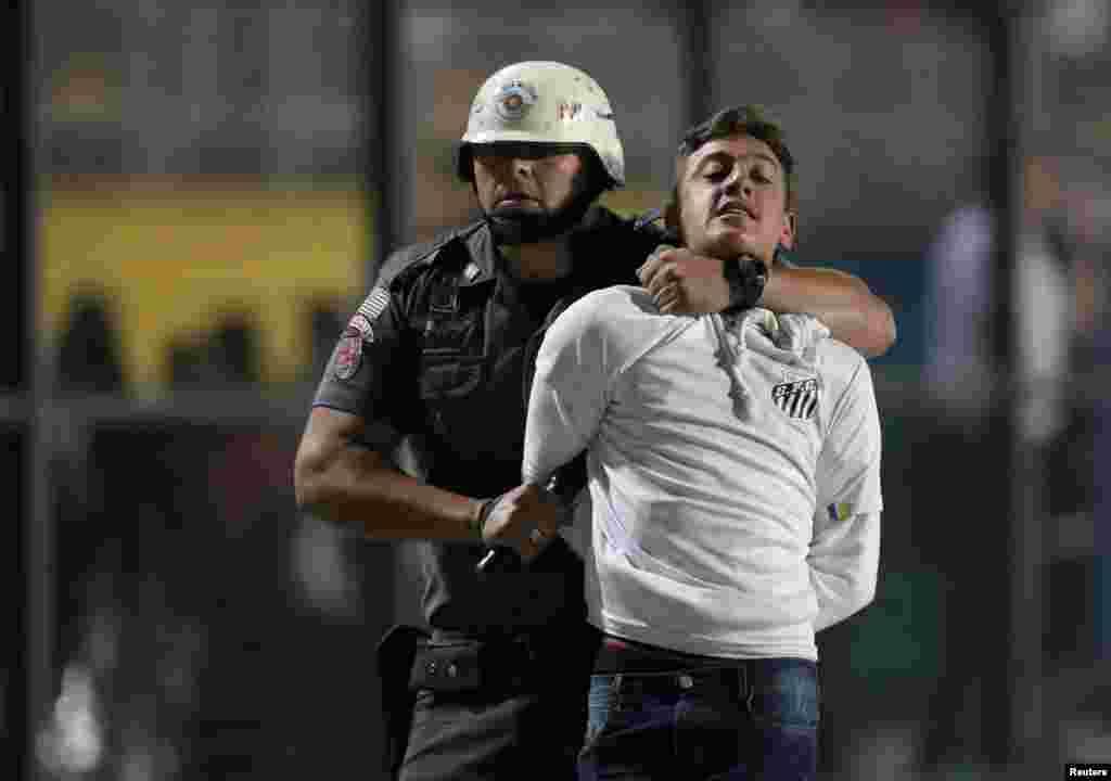 ប៉ូលិសម្នាក់ចាប់ខ្លួនអ្នកគាំទ្រក្លឹបកីឡាករបាល់ទាត់ Santos ម្នាក់អំឡុងការប្រកួតជាមួយនឹងក្រុមមកពីក្លឹប Independiente ក្នុងទីក្រុង Sao Paulo ប្រទេសប្រេស៊ីលកាលពីថ្ងៃទី២៨ ខែ សីហា ឆ្នាំ ២០១៨។