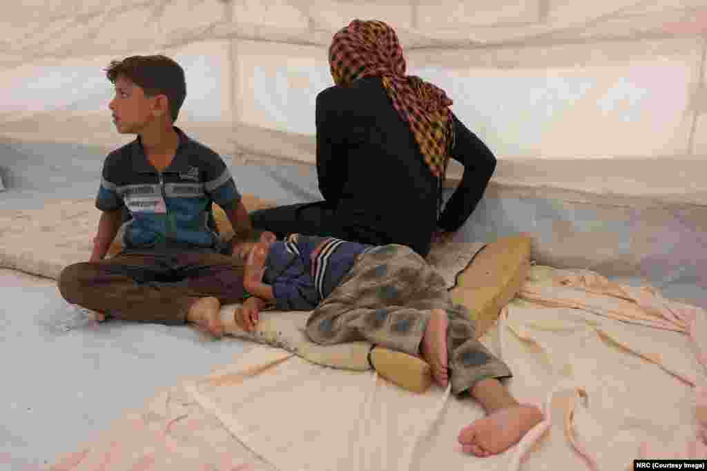 "Mohammed (9, sitting up) told NRC, ""My feet were very painful and tired after having to run all night."" Ishwaq, her husband and their three children, all under the age of 12, managed to escape Fallujah on May 23, 2016. They ran during the night for three hours before arriving at the border checkpoint where they raised white flags made of cloths so they wouldn't be shot at."