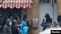 برسلز کے علاقے مولن بیک کے ایک مکان پر چھاپے کے دوران گلی میں نقاب پوش پولیس اہلکار موجود ہیں