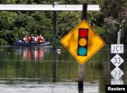 A rescue team navigates its boat through the flooded streets as the Tar River crests in the aftermath of Hurricane Matthew, in Princeville, North Carolina, Oct. 13, 2016. Matthew delayed the launch of a weather satellite that will help save lives by better forecasting hurricanes and other storms, NOAA officials say.
