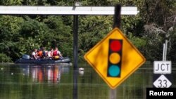 A rescue team navigates its boat through flooded streets as the Tar River crests in the aftermath of Hurricane Matthew, in Princeville, North Carolina, Oct. 13, 2016.