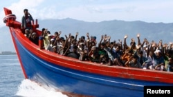 FILE - Ethnic Rohingya refugees from Myanmar wave as they are transported by a wooden boat to a temporary shelter in Krueng Raya in Aceh Besar, Indonesia, April 8, 2013.