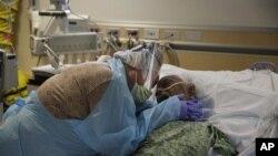 Bà Romelia Navarro, 64, khóc khi ôm chồng, ông Antonio, lần cuối khi ông sắp qua đời vì COVID-19 tại Bệnh viện St. Jude ở Fullerton, bang California