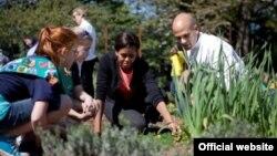 La primera dama junto a su asesor en las iniciativas de alimentación suladable, Sam Kass y una estudiante en el jardín presidencial.