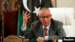 FILE - Libya's Prime Minister Ali Zeidan speaks during a joint news conference with Oil Minister Abdelbari al-Arusi at the Prime Minister's Office in Tripoli.