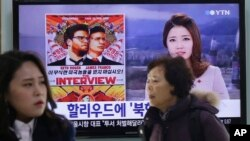 People pass a TV screen showing a news report on Sony Picture's 'The Interview,' at the Seoul Railway Station in South Korea.