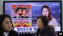 "FILE - People walk past a TV screen showing a poster of Sony Picture's ""The Interview"" in a news report, at the Seoul Railway Station in Seoul, South Korea."