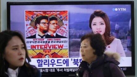 首尔火车站上关于影片《采访》的电视新闻报道,荧屏上有该电影的海报
