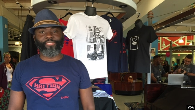 Haitian-American vendor Roe Michel sells inspirational t-shirts with empowering messages at the Caribbean Marketplace. He is wearing his best-seller, the Super Haitian t-shirt in Little Haiti, Miami, Florida. (Photo: S. Lemaire / VOA)