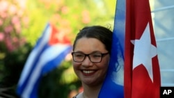 A woman holds a Cuban flag while celebrating the restoration of diplomatic relations between the island nation and the United States, in the courtyard of the Cuban Embassy in Santiago, Chile, Wednesday Dec. 17, 2014. After a half-century of Cold War acrim