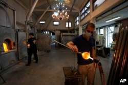 A glass-worker finishes a glass artistic creation in a factory in Murano island, Venice, Italy, Oct. 7, 2021.