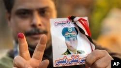 """Một cử tri vừa bỏ phiếu, cầm ảnh của Bộ trưởng Quốc phòng, Tướng Abdel-Fattah el-Sissi với hàng chữ """"Sissi, tôi muốn ông là tổng thống của tôi"""" trước một phòng phiếu ở Cairo, 15/1/14"""