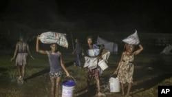 Penyintas gempa berjalan di tengah hujan tropis Grace di kamp pengungsi Les Cayes, Haiti, Senin, 16 Agustus 2021. (AP Photo/Joseph Odelyn)