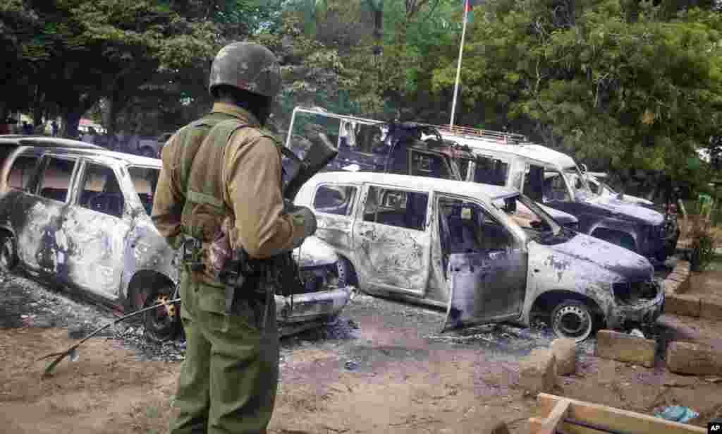 Keniyaning Mpeketoni shahri yaqinidagi Kibaoni qishlog'ida jangarilar tomonidan vayron qilingan avtomobillar, 16-iyun, 2014-yil.