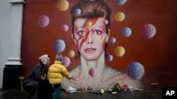 Una mujer y un niño colocan flores en un mural de David Bowie, el cantante británico que murió este lunes.